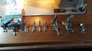 Extra presser feet from the Touch 'n' Sew (L-R) button foot, zipper, special purpose, 3 general purpose, multi-slotted bias binder, ruffler, unknown